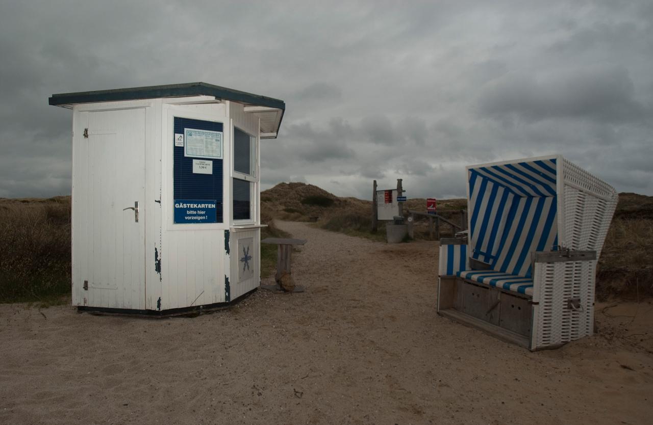 """Auf dem Kontrollhäuschen der Kurkarten am Strandübergang der Buhne 16 in Kampen hangt ein Schild mit der Aufschrift: ,,Bitte zeigen Sie hier Ihre Gästekarten vor!"""""""