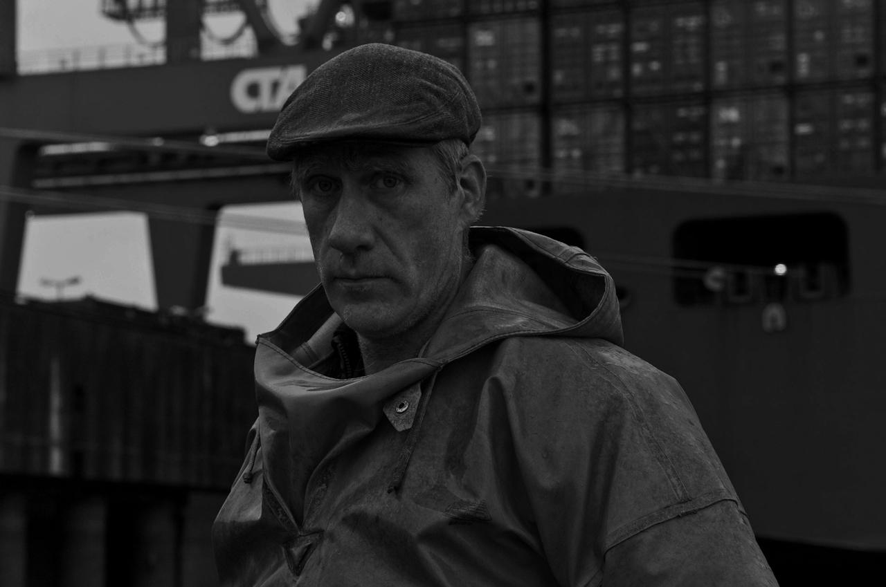 """Elbfischer Olaf Jensen in seinem Boot """"Butt"""" vor Containerschiff am CTA Containerterminal Altenwerder. Dies ist ein ruhiges Gewässer viel eher gibt eine Chance auf Fang als in der starken Strömung in der mehrfach ausgebaggerten Elbe."""