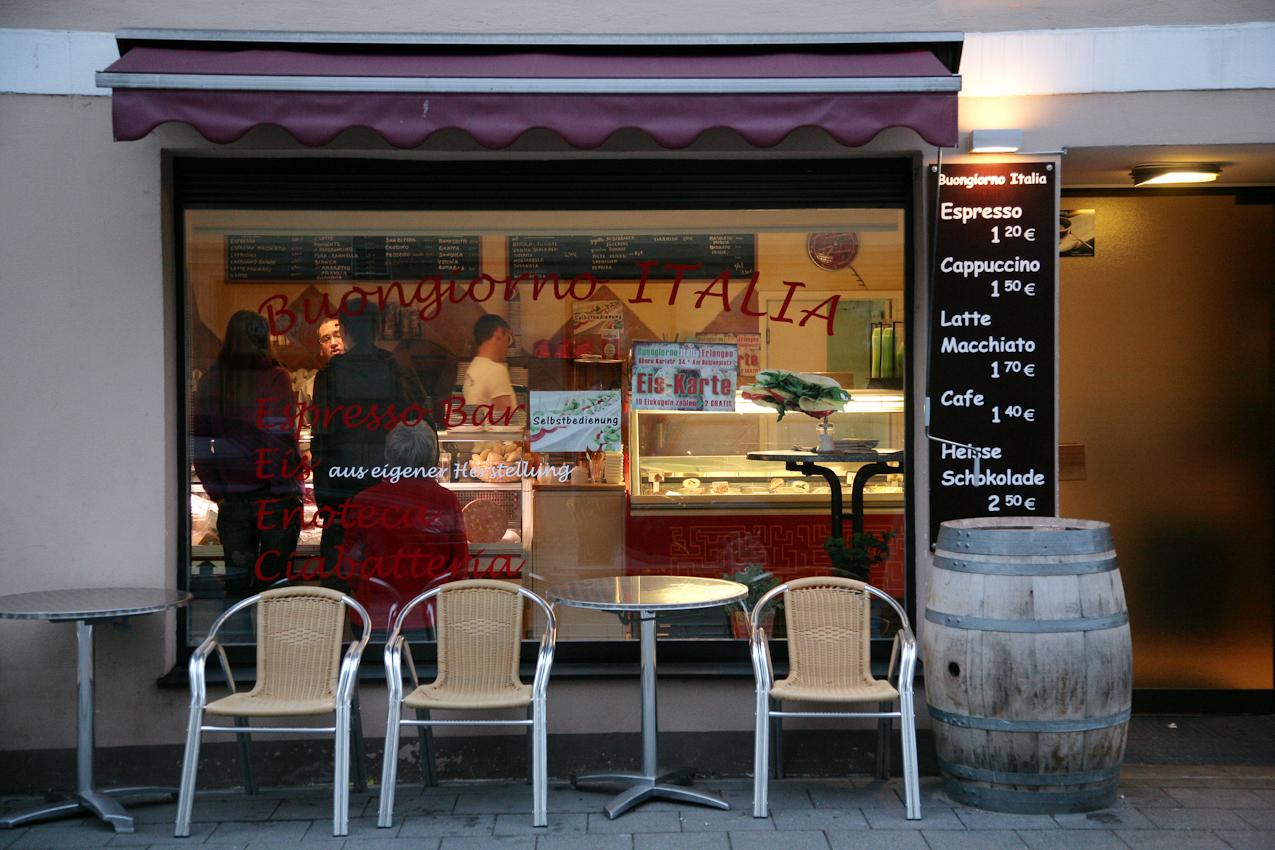 Restaurant Buongiorno Italia (Ciabatteria, Enoteca und Eis-Cafe) in Erlangen, Obere Karlstrasse 34, Außenansicht des Restaurants um 20:38 Uhr, Kellner Antonio (links) bei der Ciabatta-Bestellung durch ein Pärchen, Roberto Particolare (rechts,Bruder des Mitinhabers Fernando Particolare) aushilfsweise beim Geschirr sortieren, auf dem Fensterbrett sitzend und die Szenerie beobachtend meine Frau Susanne Cindric.