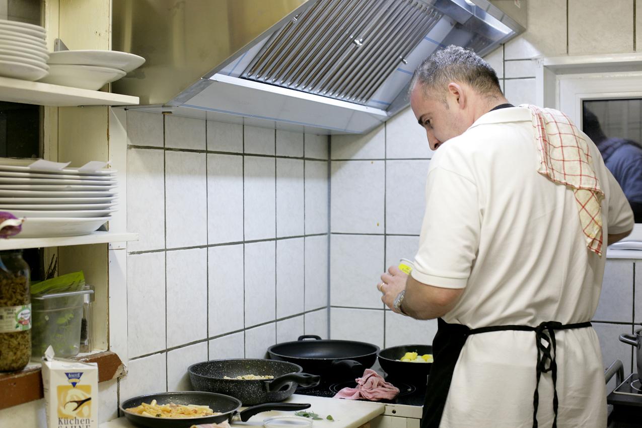 Restaurant Buongiorno Italia (Ciabatteria, Enoteca und Eis-Cafe) in Erlangen, Obere Karlstrasse 34, Fernando Particolare (Ehemann der Inhaberinn Maria Rosaria Particolare und Koch) beim Kochen verschiedener Abendessen Hauptgerichte in der Küche des Restaurants.