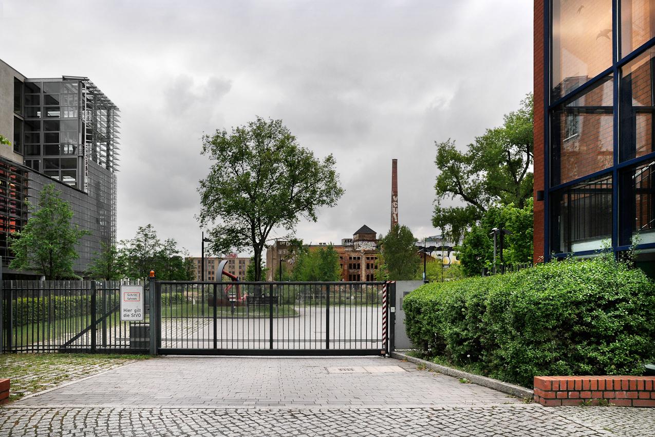 Blick von der Holzmarktstraße in Berlin Friedrichshain nach Süden über die Spree hinweg zur Köpenicker Straße in der Luisenstadt, Berlin Mitte. Der Maihimmel wird durch dichte graue Wolken beherrscht. Am rechten und linken Bildrand sind im Vordergrund Neubauten und für zeitgemäße Nachnutzungen umgestaltete historische Industriebauten zu erkennen. In der Bildmitte sieht man im Hintergrund neben einer Abrissbrache die denkmalgeschützte, zwischen 1893 und 1922 errichtete und seit den 1990er Jahren ungenutzte Kunsteisfabrik Berlin Mitte. Die Immobilie direkt am Spreeufer mit den historischen Produktions- und Lagergebäuden der früheren Norddeutschen Eiswerke AG mit dem zu erkennenden Schornstein des Kesselhauses, der Turmspitze der alten Kältemaschinenhalle und den Kuhlhäusern unterliegt aufgrund ihrer attraktiven Lage einem hohen Spekulationsdruck. Die seit 1995 mit der Verwaltung und Entwicklung der Immobilie betraute Treuhand Liegenschaftsgesellschaft mbH strebt mit wachsendem Eifer die Zerstörung des  denkmalgeschützten Bauensembles an, um hier Platz für profitable Neubauten zu schaffen.