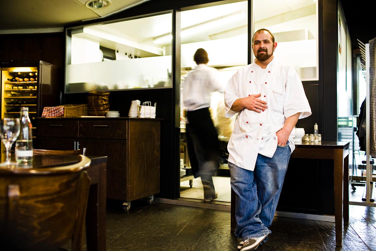 """""""Die Ruhe vor dem Sturm"""" Ein Koch im Restaurant im Foyer der Kammerspiele Bochum nutzt die Gelegenheit um sich zwischen den Anstürmen zu regenerieren. Sein Arbeitskollege im Hintergrund leitet schon die nächste anstrengende Runde ein."""