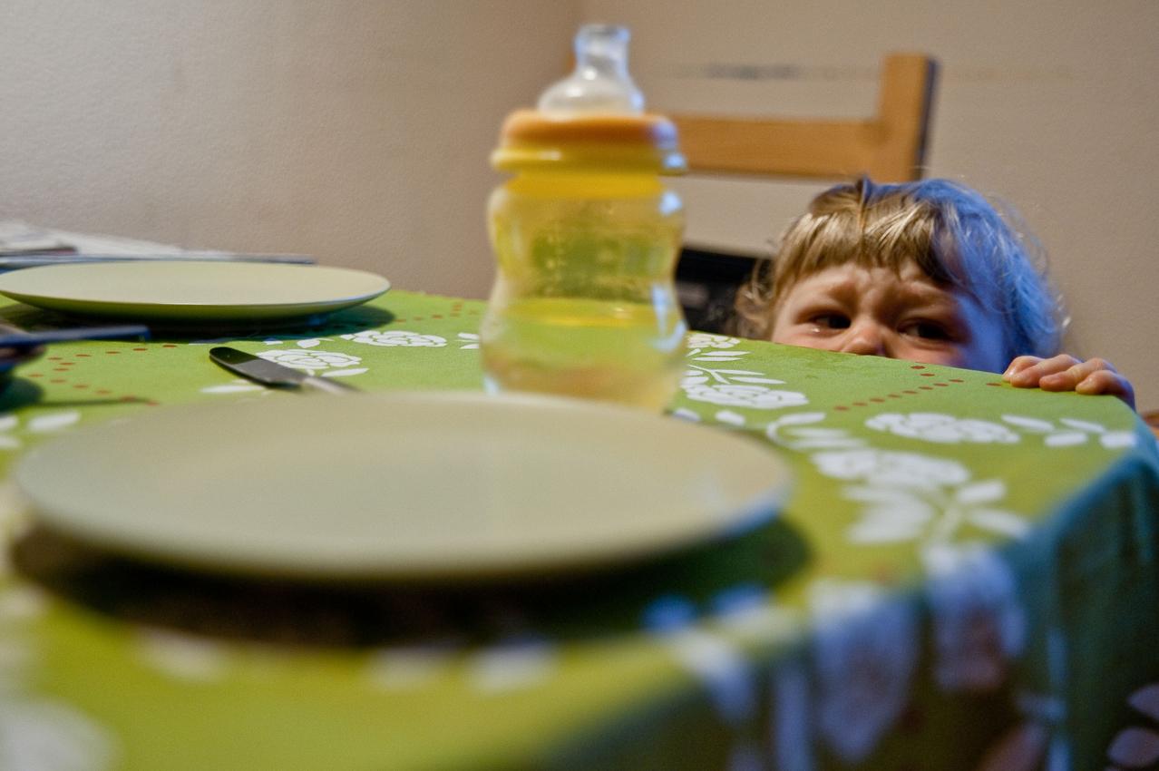 """7.11 Uhr, Küche: Direkt nach dem Aufstehen. Der kleine Levin (14 Monate) hatte eine unruhige Nacht und ist bereits vor dem gemeinsamen Familienfrühstück quengelig und weinerlich. Das Foto wurde am 07.05.2010 für das Projekt """"Ein Tag Deutschland"""" aufgenommen im Rahmen einer Fotoserie über das Alltagsleben einer Kleinfamilie im Dorf Maintal-Wachenbuchen, 15 Km östlich von Frankfurt am Main. Bei der Serie geht es darum den normalen Alltag eine Kleinfamilie zu zeigen, bei der nach klassischem Rollenmodell vorwiegend die Mutter für die Erziehung der Kinder zuständig ist. Die Mutter arbeitet freiberuflich als Fotografin, der Vater geht einem klassischen Bürojob nach und arbeitet jeden Tag 20 km entfernt. Miteinander, Nebeneinander und Gegeneinander sind das Thema der Serie mit Fokus auf der Beziehung der Geschwister untereinander, die den Familienalltag maßgeblich mitbestimmen. Die Serie über den Familienalltag ist als Langzeitprojekt angelegt. Die Fotos entstanden alle in der Wohnung der Familie, die Dreh- und Angelpunkt des Familienlebens ist. Zur Familie gehören der Vater Thomas Schäfer, die Mutter Meike Fischer (die auch fotografiert hat), die 5-jahrige Tochter Nia und der 14 Monate alte Sohn Levin."""