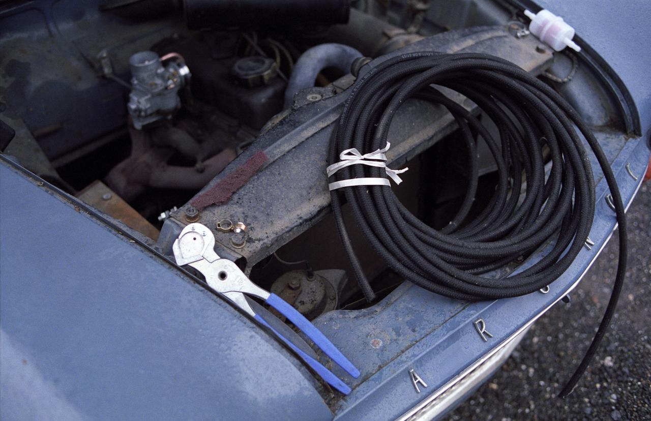 Der Motorraum des SIMCA Aronde P 60 (Bj. 1959) wahrend des Vergasereinbaues. Im Hintergrund ist der neu eingebaute Vergaser zu erkennen, Werkzeug und Benzinschlauch sind wahrend der Arbeiten  auf dem Motorraum abgelegt.