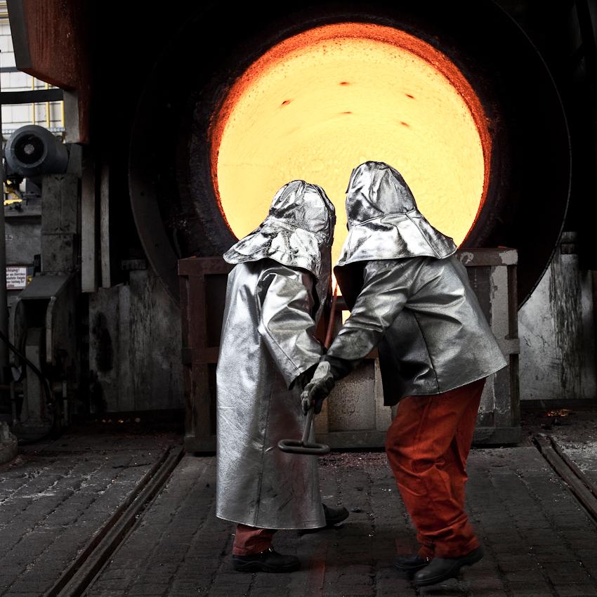 KME Germany ist einer der weltweit größten Hersteller von Erzeugnissen aus Kupfer und Kupferlegierungen. Das Werk in Osnabrück wurde 1873 als Draht- und Stiftfabrik Witte und Kämper in Osnabrück gegründet. Das Foto zeigt zwei Arbeiter in Hitzeschutzkleidung beim Entfernen der Schlacke aus dem Hochofen. Das Foto entstand am 7. Mai um 11.07 Uhr in der Gießerei der KME Germany in Osnabrück.