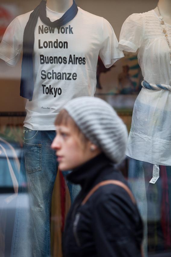 """Das Schanzenviertel in Hamburg ist wohl mit das angesagteste Quartier in Deutschland. Einst ein Refugium fur alternative Lebensformen und Ort autonomer politischer Organisation hat es sich mittels staatlicher Umstrukturierungsprogramme zum Ausgeh- und Shopping Paradies entwickelt. Wer heut zu Tage etwas auf sich hält, geht in """"Die Schanze"""". Die Ironie dieses T-Shirts, welches schon seit Jahren in der Suasannestraße in den Auslagen zu sehen ist, hat sich schon lange überholt."""