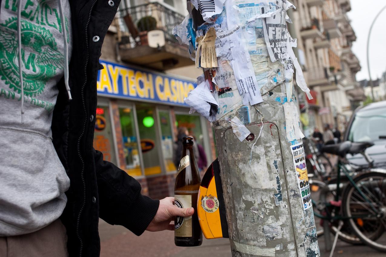 """Das Schanzenviertel in Hamburg ist wohl mit das angesagteste Quartier in Deutschland. Einst ein Refugium fur alternative Lebensformen und Ort autonomer politischer Organisation hat es sich mittels staatlicher Umstrukturierungsprogramme zum Ausgeh- und Shopping Paradies entwickelt. Wer heut zu Tage etwas auf sich hält, geht in """"Die Schanze"""". Das typische Erscheinungsbild eines Schanzenbesuchers: die Bierflasche. Hier an der Fußgängerampel an der S-Bahn Sternschanze."""