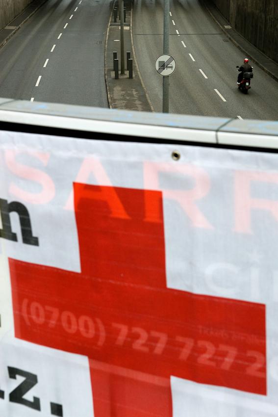07.05.2010, 11:11 Uhr. Deutschland, Berlin. Alexanderplatz. Blick in die Unterführung an der Grunerstrasse Richtung Westen. Im Vordergrund ein Banner des Roten Kreuz zur Bewerbung von Blutspenden. Auf der Straße fährt ein Mopedfahrer aus dem Bild.