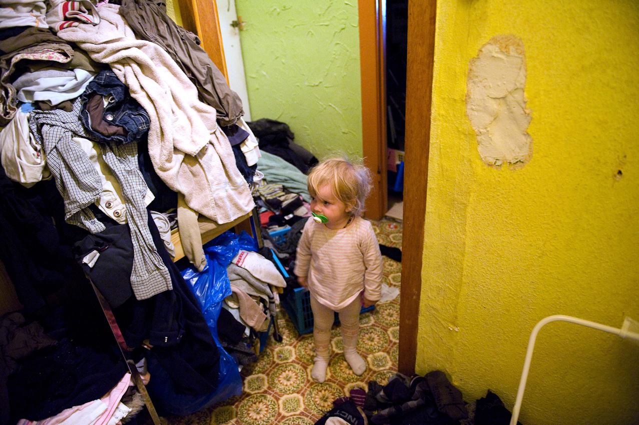 """Josefine (2 Jahre) steht neben einem Berg Schmutzwäsche. Alltag in einer Großfamilie bedeutet ständiger Trubel zu Hause, Berge von Wäsche, mehrere Kilo Lebensmittel, wenig Geld fur Hobbys oder Extraausgaben und selten Ruhe. Dennoch gibt es auch viele schöne Seiten an diesem Familienmodell. ,,Die sechs Kinder waren alle geplant,"""" sagt Steffi. ,,Der Zusammenhalt in der Familie und Austausch untereinander ist schön."""""""