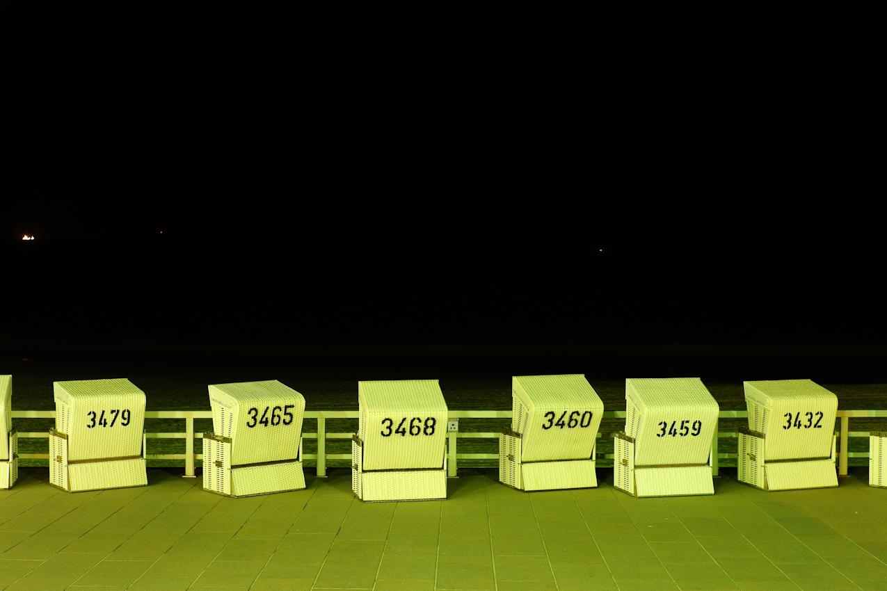 Strandkoerbe auf der Westerlaender Strandpromenade im naechtlichen Kunstlicht, der vor drei Stunden untergegangenen Sonne zugewandt. Hinten links Licht des Hopperbaggers, der draussen vor der Kueste Sand aufnimmt.
