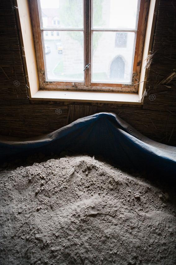 Sanierung eines Fachwerkhauses von 1582 in Arnstadt, Thüringen. Zwischen den Deckenbalken und auf den historischen Holzkassetten lag Deckenschüttung, letztlich Staub und Dreck. Nach und nach wird diese Schüttung ausgeschaufelt, zwischengelagert, ein Fehlboden mit Rieselschutz montiert und dann die Schüttung wieder eingebracht.