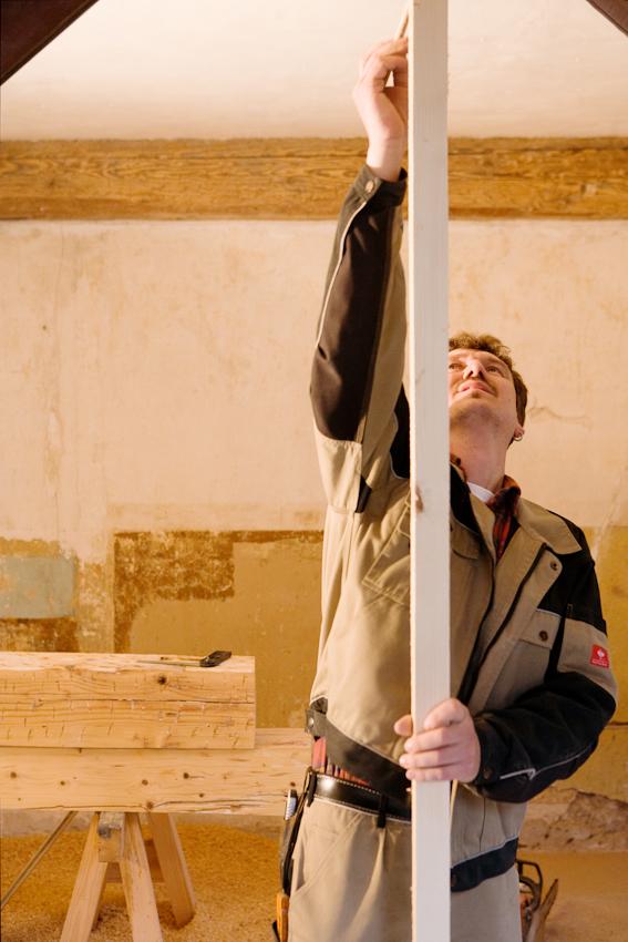 Sanierung eines Fachwerkhauses von 1582 in Arnstadt, Thüringen. Thorsten Reimer ermittelt den genauen Standort und Maß der aufzustellenden Holzsäule, die aus einem alten Deckenbalken entstanden ist.