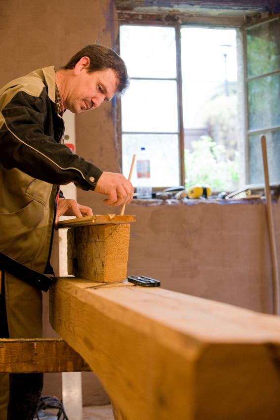 Sanierung eines Fachwerkhauses von 1582 in Arnstadt, Thüringen. Dieser Balken ist mindestens 200 Jahra alt und wird von Thorsten Reimer von Hand zu einer Säule und einem querliegenden Kapitell bearbeitet, die einen Unterzug stützen werden.