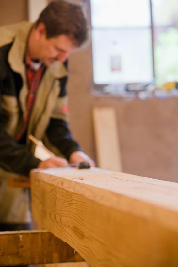 Sanierung eines Fachwerkhauses von 1582 in Arnstadt, Thüringen. Dieser Balken ist mindestens 200 Jahra alt und wird von Thorsten Reimer von Hand zu einer Säule und einem querliegenden Kapitell bearbeitet, die einen Unterzug stützen werden. In Farbe, Patina und Qualität ist das alte Fichtenholz mit modernem schnellwachsendem und expressgetrocknetem Holz nicht zu vergleichen.