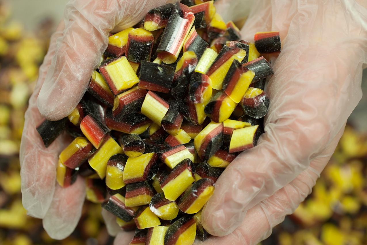 """Hamburg - im """"Bonscheladen"""" im Hamburger Stadtteil Ottensen von Uwe Sponnnagel   genannt Spoon- werden feine Bonbons und Fudge von Hand hergestellt. - hier entsteht gerade der Spezial-Bonbon Tricolori-Deutschland. Die Zutaten werden genau nach Rezeptur abgewogen. Das sind Apfelholunder (schwarz), Erdbeere (rot), und  Zitronenöl (gelb). Die Glucose wird zum Kochen gebracht, dann wird die Zuckermasse auf dem Kühltisch ausgegossen. die jeweilige Geschmacks- und Farbrichtung wird beigemischt. Die drei entstandenen großen Bonbons werden zusammengedrückt, unter einer Wärmelampe  am schnellen Abkühlen gehindert. Von Hand wird der nun entstandene Großbonbon in die Lange gezogen. Die Stangen werden auf Länge geschnitten und. nach dem endgültigen Abkühlen und hart werden,  mit Spezialmessern in Bonbongröße zerhackt."""
