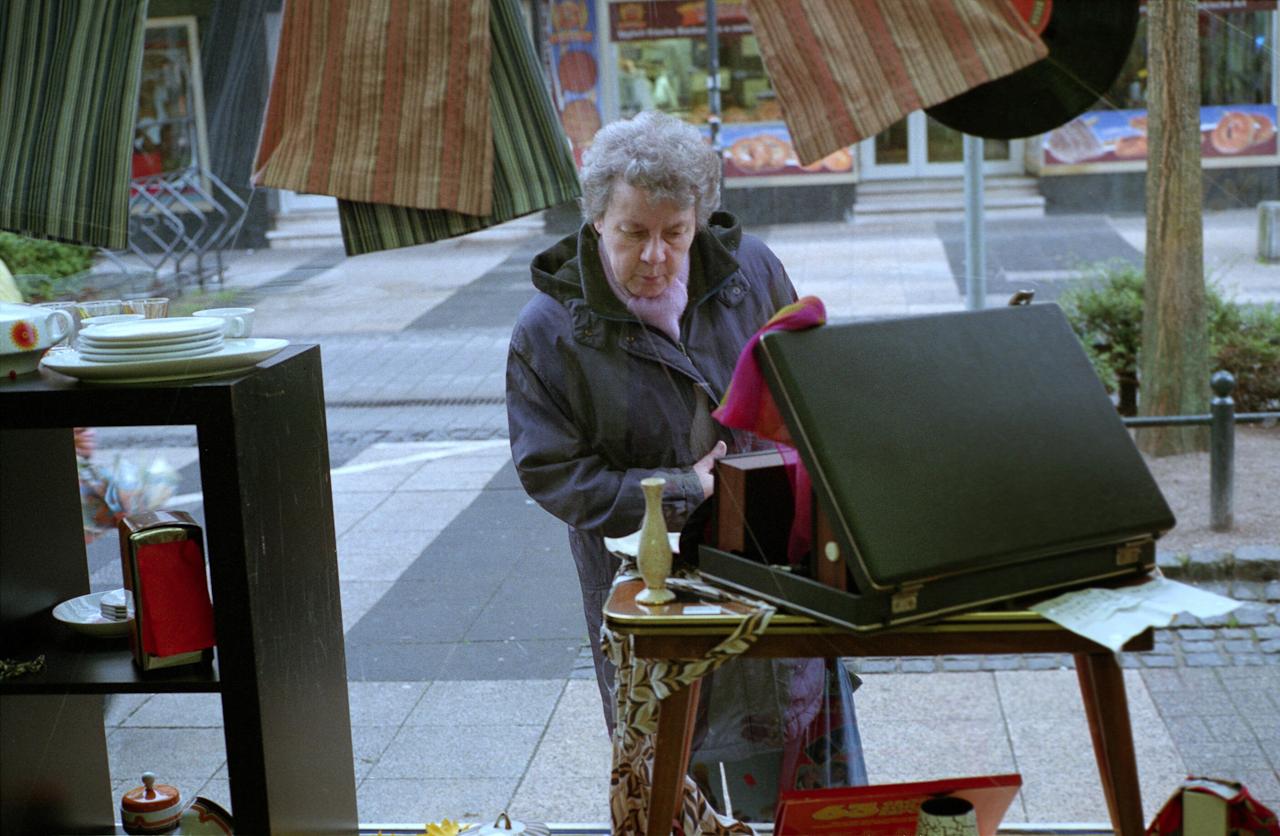 Frau schaut in das Schaufenster des Diakonieladens in der Fußgängerzone der Herner Innenstadt.