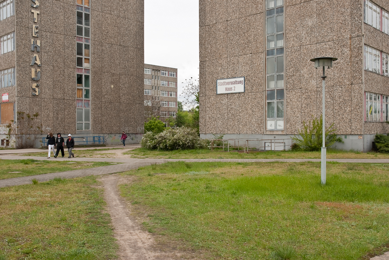 DEU, Deutschland, Brandenburg, Eisenhuttenstadt. Grünanlage vor der Stadtverwaltung neben dem ehemaliges Gastehaus in einem Plattenbau an der Karl-Marx-Strasse Ecke Strasse der Republik.