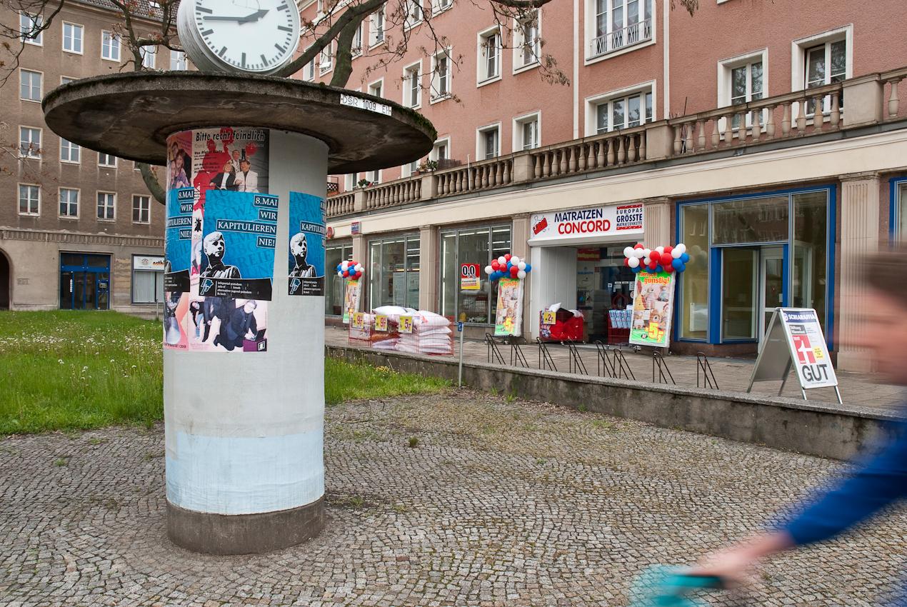 DEU, Deutschland, Brandenburg, Eisenhüttenstadt. Litfasssäule mit einem reaktionären Plakat der Alternative Jugend Potsdam zum 8. Mai (Wir kapitulieren nie!)  vor einer Ladenpassage an der Karl-Marx-Strasse Ecke Strasse der Republik.