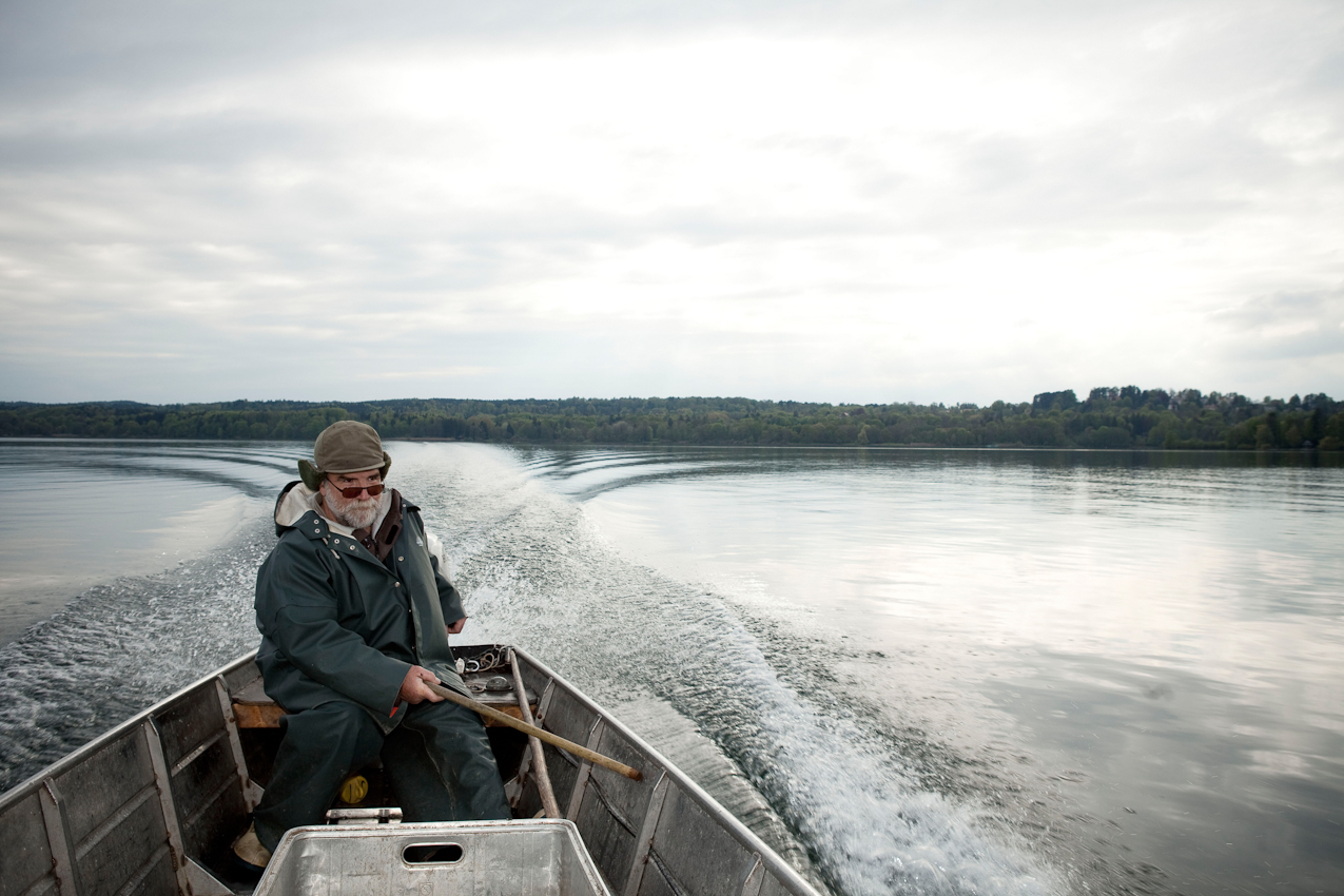 Der Fischer Johann Schuster abends am 7. Mai 2010 in seinem Boot auf dem Nachhauseweg auf dem Starnberger See, nachdem er die vormittags eingeholten Netze wieder ausgelegt hat und die Reusen geprueft hat.