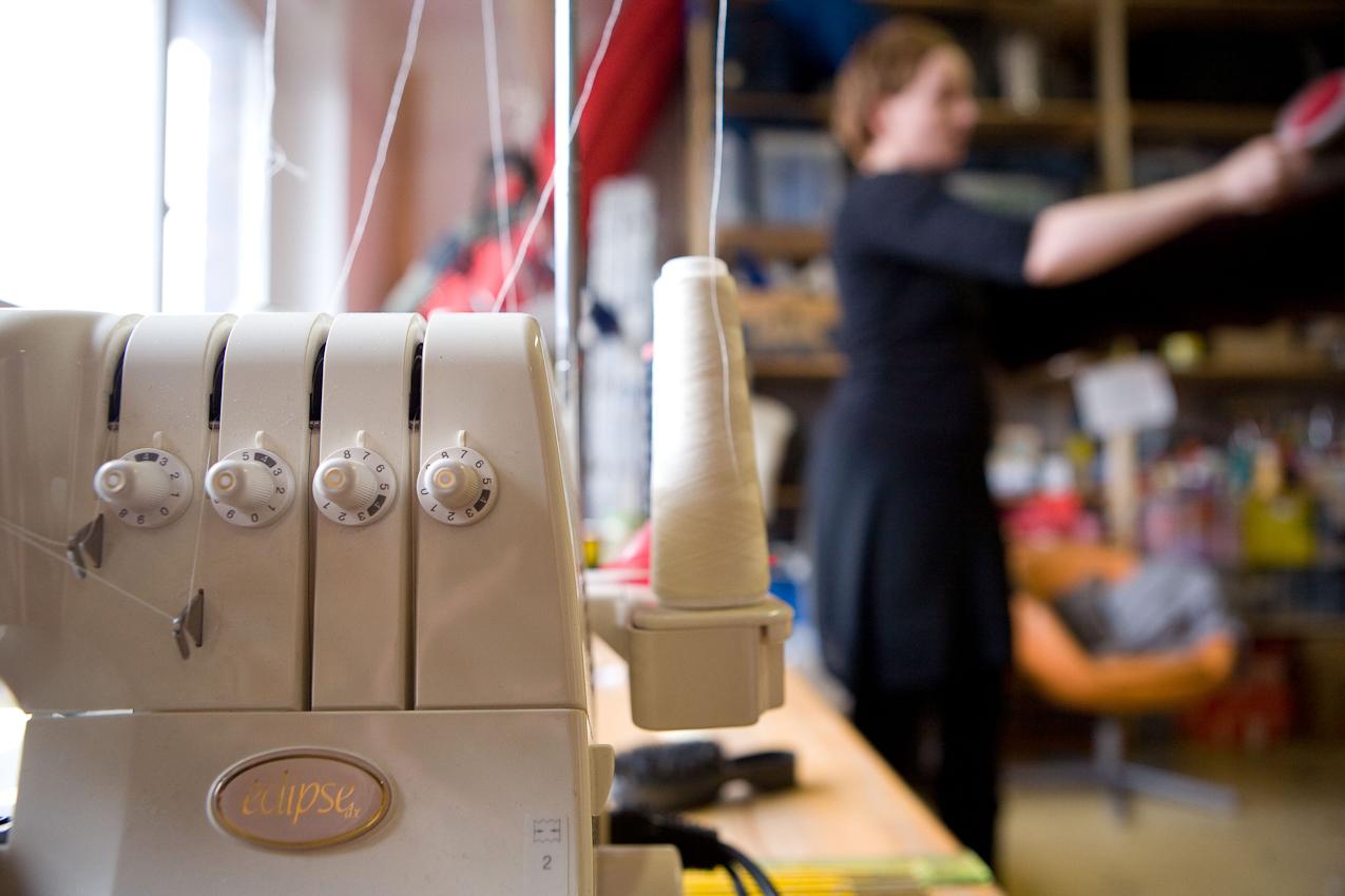 """Besuch bei Kuenstlern des Kreativ-Netzwerkes """"Made in Cologne"""". """"Made in Cologne"""" hat es geschafft, aus der virtuellen Welt zu realen monatlichen Treffen zu gelangen. Eine gute Gelegenheit fuer einen Blick hinter die Kulissen. Das Atelier der Kuenstlerin """"Ivy"""" zeigt die spezielle Nahmaschine, mit der """"Ivy"""" ihre Figuren verbindet und auch Figuren anderer flickt. Im Hintergrund erkennt man schemenhaft die Kuenstlerin in ihrem Atelier im Kunstwerk Koeln in der Deutz-Muelheimer Strasse 127-129, 51063 Koeln. Aufnahmezeitpunkt: 07.05.2010, 13:16 Uhr"""