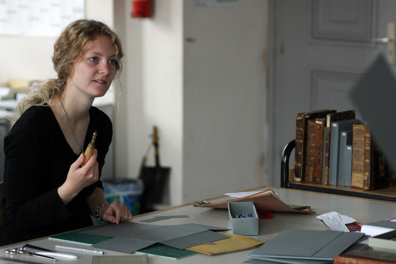 Vanessa Orlik ist studentische Hilfkraft der Buchbinderei der Universitätsbibliothek Mannheim. Die Werkstatt ist zuständig sowohl für das Buchbinden (meisten sind neue Bücher) als auch für Konservierung und Reparieren der alten Bücher, die vor 1850 erschien sind. Die Hiwi ist nur für Konservierung der alten Bucher zuständig. Gerade bastelt Vanessa Orlik eine Verpackung aus Pappe für ein altes Buch, weil viele Bücher einen extra Schutz brauchen. Das Fotos wurde um 10:33 an einem ihr ganz normalen Arbeitstagen aufgenommen.
