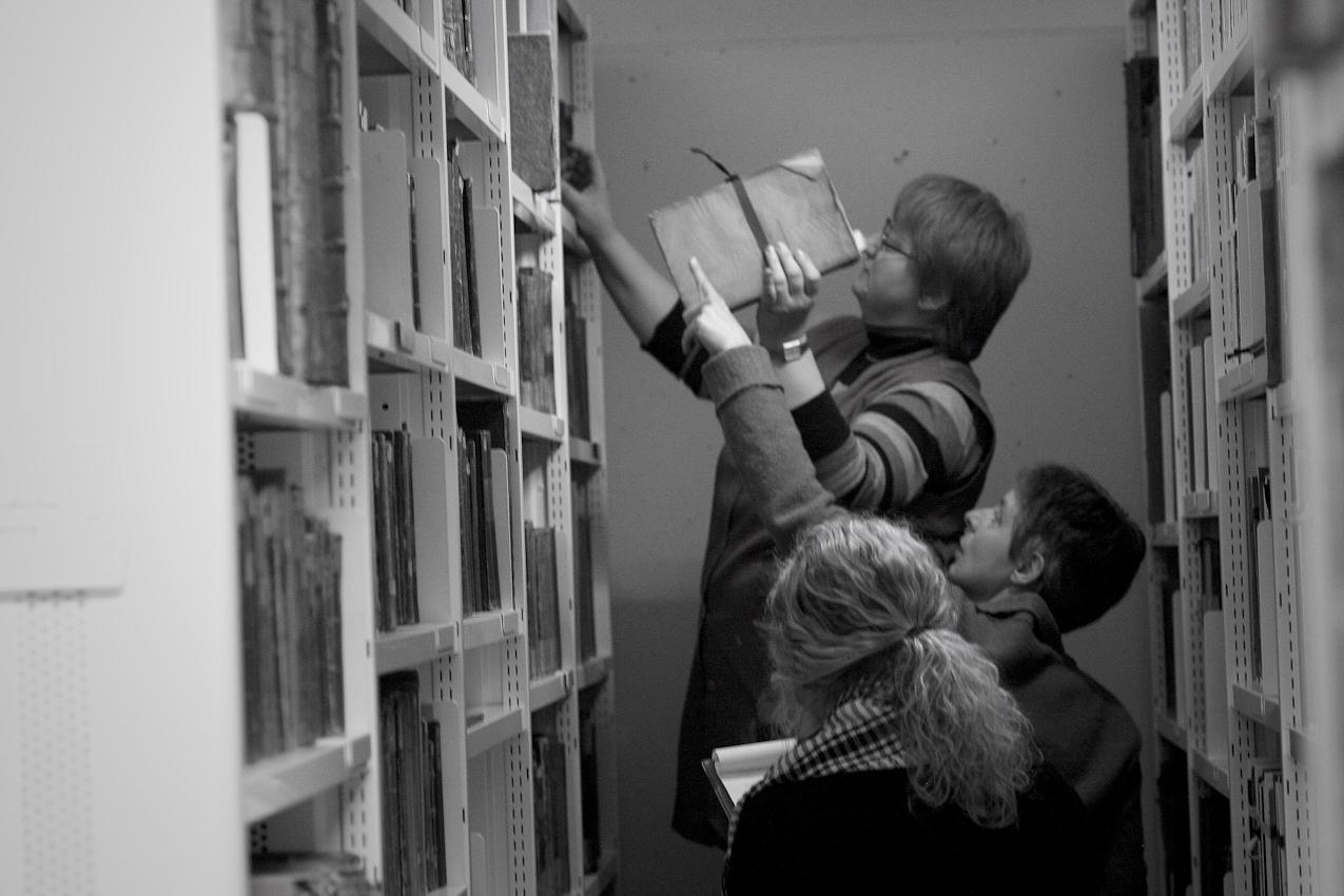Susanne Kaerner, Betreuerin der Buchbinderei der Universitätsbibliothek Mannheim; Barbara Mazurek, Mitarbeiterin, Vanessa Orlik, studentische Hilfskraft. Die Werkstatt ist zuständig sowohl für das Buchbinden (meisten sind neue Bücher) als auch für Konservierung und Reparieren der alten Bücher, die vor 1850 erschien sind.  Gerade sind sie in der Tiefmagazine der Universitätsbibliothek Mannheim, wo die alten Bücher unter besonderen Bedingungen (Temperatur, Feuchtigkeit etc.) bewahren werden. Sie messen die Bücher, um Verpackungen für sie zu bestellen. Das Foto wurde um 12:11 aufgenommen.
