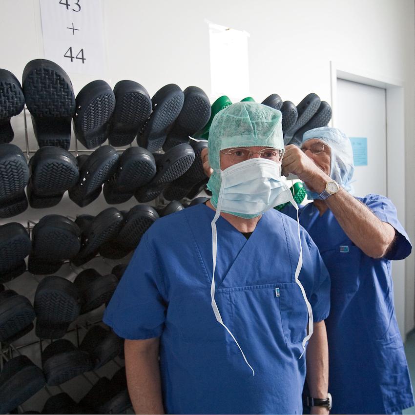 Prof. Samii bindet dem Fotografen Karl Johaentges im Umkleideraum und Schleuse persönlich einen Mundschutz um.