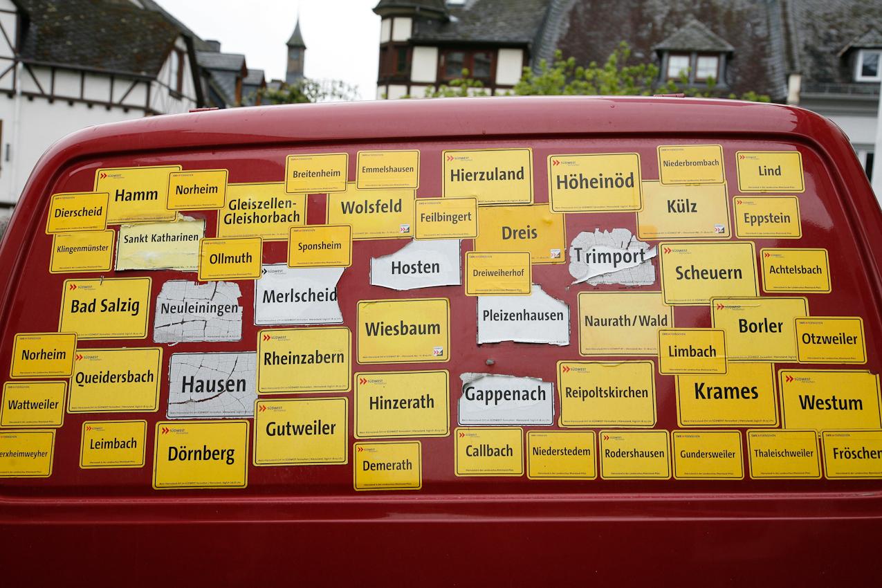 Heckklappe eines Lieferwagens mit Ortsschildercollage geparkt vor der evangelischen Kirche in Winningen.