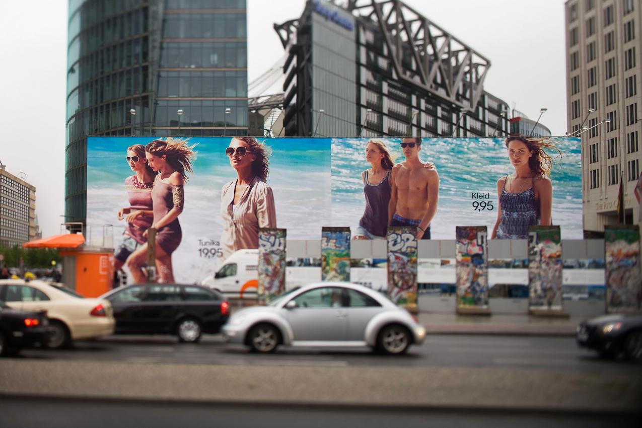 """""""Unsere Werte - Großflächenwerbung in öffentlichen Räumen"""":  Berlin, 7.5.2010, Eine Großflächenwerbung der Modefirma H + M steht an einer Strasse auf dem Potsdamer Platz hinter einzelnen Teilen der Berliner Mauer. Dahinter befindet sich das Sony Center, der Bahn-Tower und das Hotel Ritz Carlton."""