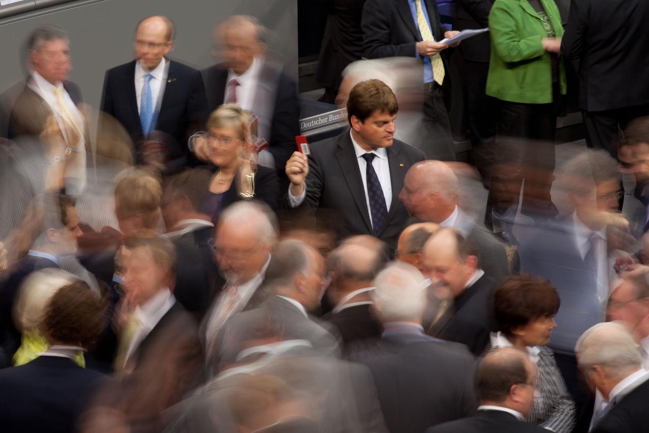 Reichstag, Plenarsaal. Abstimmung zur Bewilligung der Griechenlandkredite. Mann weißt mit erhobener Abstimmungskarte den Fraktionsmitgliedern den Weg zur Urne.