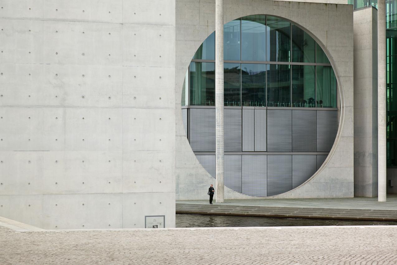 Marie-Elisabeth-Lüders-Haus. Einzelner Mann vor der runden Fensterfront des Marie-Elisabeth-Lüders-Hauses.