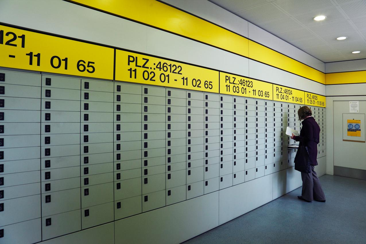 Junge Frau bei der Leerung eines der Postschließfächer im Postamt Sterkrade, Oberhausen.