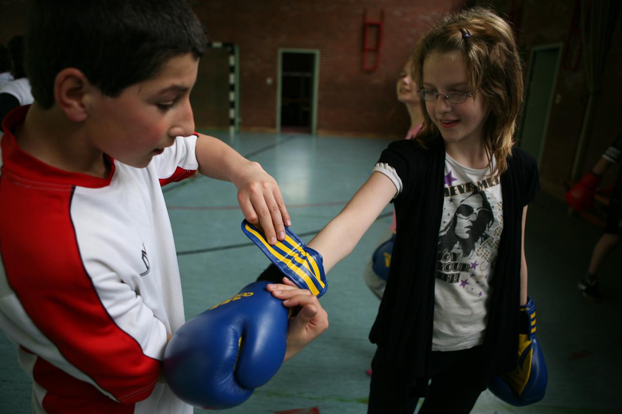 Übung, aber auch Fair Play macht den Meister: Mesut hilft Chayenne beim Anziehen der Boxhandschuhe.
