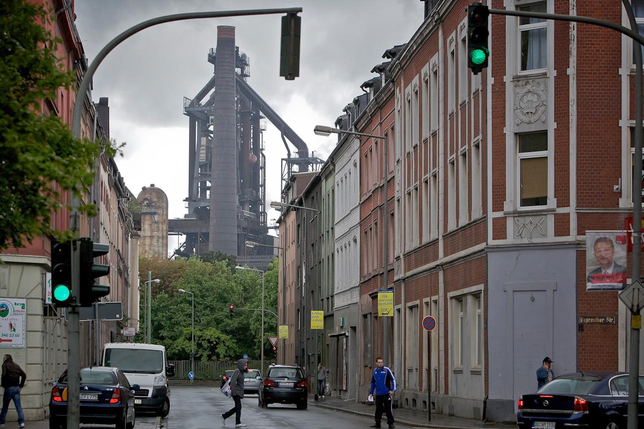 """Die Dieselstraße in Duisburg-Bruckhausen mit Blick auf den Hochofen 4 des ThyssenKrupp-Werks. Schwerindustrie und Wohnhäuser - ein Miteinander, das das Ruhrgebiet jahrzehntelang geprägt hat und nur noch hier zu finden ist. Als die ersten Gastarbeiter kamen, um in den Hochöfen und Stahlwerken zu arbeiten, ließen sie sich gegenüber dem ThyssenKrupp-Werk nieder. Später folgten die Familien der Immigranten und so entstand nach und nach eine richtige ,,ausländische"""" Gemeinde. Es leben überwiegend Bürger türkischer Herkunft in dem sozialschwachen Gebiet. Mit einem Ausländeranteil von zwischenzeitlich über 50% (Ende 2009: 47,44%) stellt Bruckhausen einen der ersten Stadtteile dar, in dem Deutsche zur Minderheit wurden. Heute soll der Stadtteil teilweise abgerissen werden, um Industrie und Wohngebiete zu entflechten."""