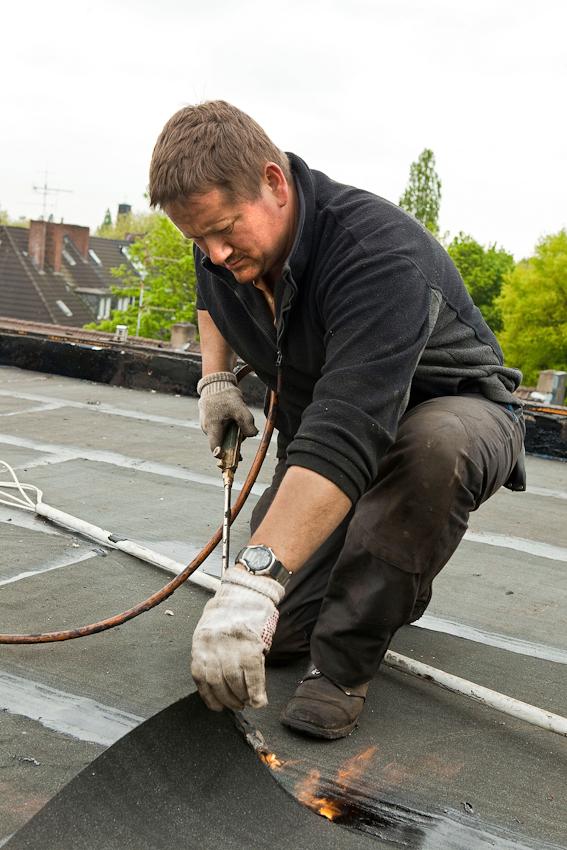 Ein Geselle trägt mit dem Brenner neue Dachpappe auf.