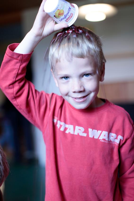 Das kitzelt so schön auf der Kopfhaut: Henning (6) lässt sich getrocknete rote Bohnen aus einem Joghurtbecher über das Haar rieseln und amüsiert sich dabei.
