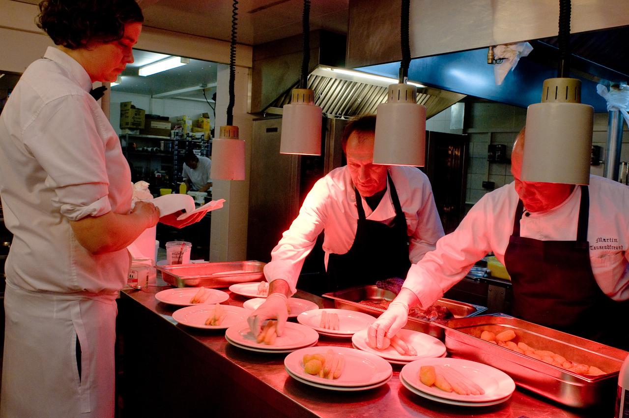 Gemeinsam richten der Küchenchef Martin Tausendfreund (r.) und der Souschef Rechou Maurer (l.) den Hauptgang einer Menu-Gruppe an. Frauke Hofert sorgt dafür, dass die Speisen schnell zum Gast gelangen.