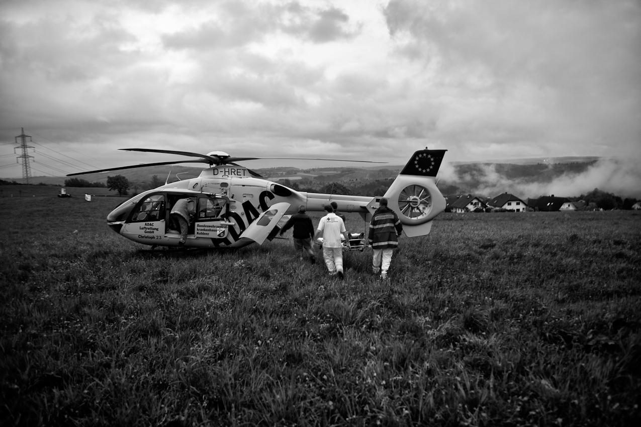 Die Besatzung bringt den Patienten zum Hubschrauber.