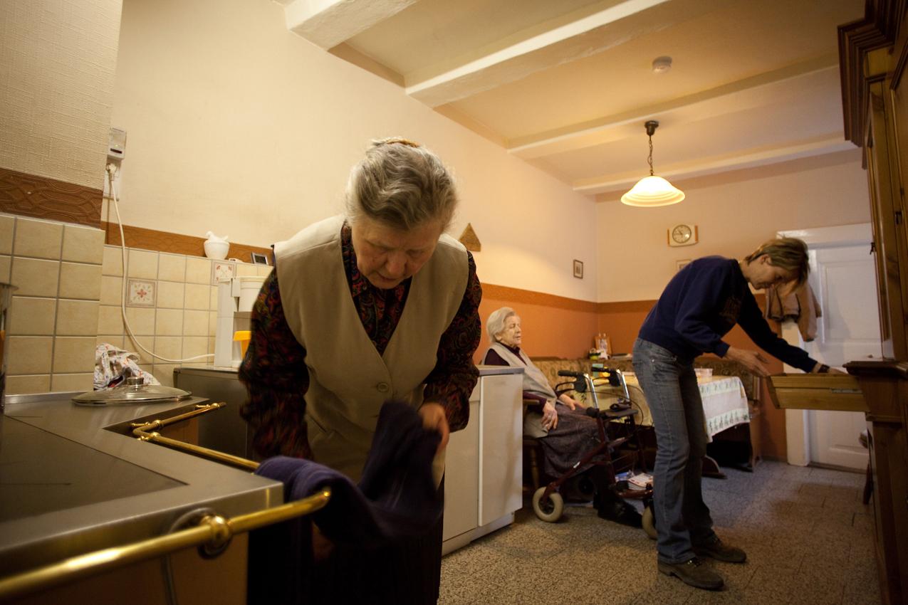 """""""3 1/2 Generationen unter einem Dach"""": Vor 2 Jahren hat Siglinde Bruns ihre 90-jährige Mutter Lisbeth bei sich zu Hause aufgenommen. Sie unterstützt und pflegt sie im arbeitsreichen Alltag so gut sie kann. Hier treffen Siglinde (vorne) und Christiane (rechts) gemeinsam in der Hofküche erste Vrobereitungen für das Mittagessen, das auf einem maßgefertigten Kachelofen mit integrierter Herdplatte zubereitet wird. Großmutter/Mutter Lisbeth leistet Ihnen am Vormittag und Nachmittag in der Küche Gesellschaft."""