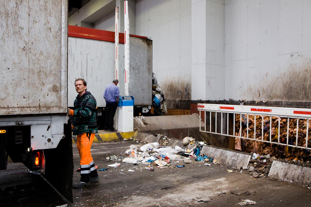Thomas Weyl holt mit einer Harke Restmüll aus seinem LKW, nachdem er den Müll aus seinem LKW durch die Schleuse in den Müllbunker entladen hat.