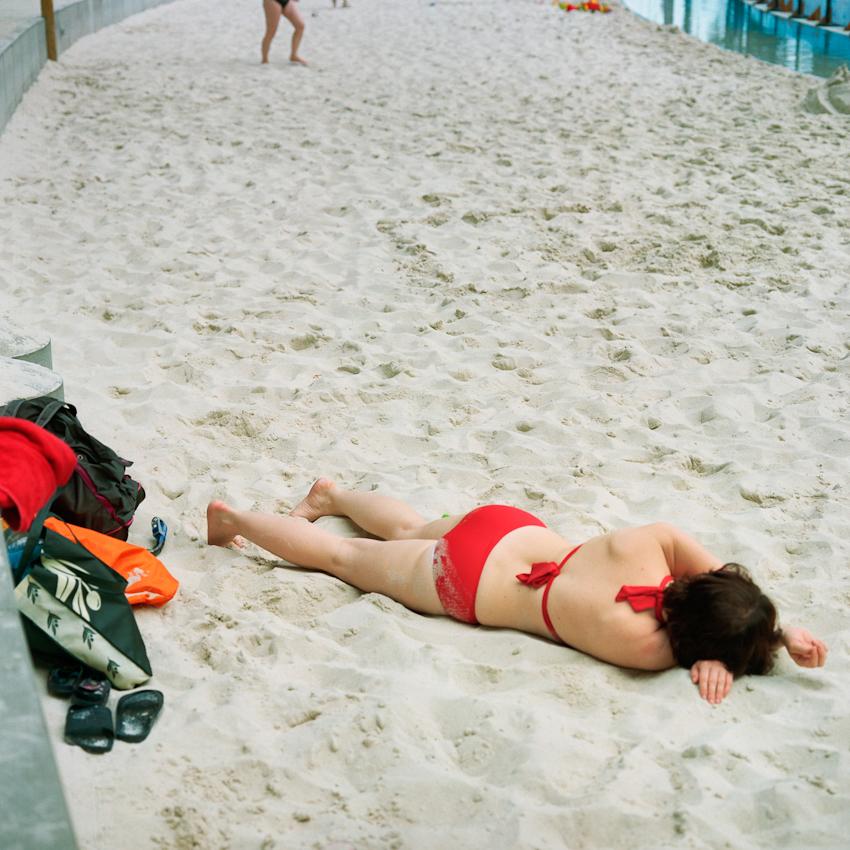 """Eine im Sand liegende Frau in der """"Südsee""""."""