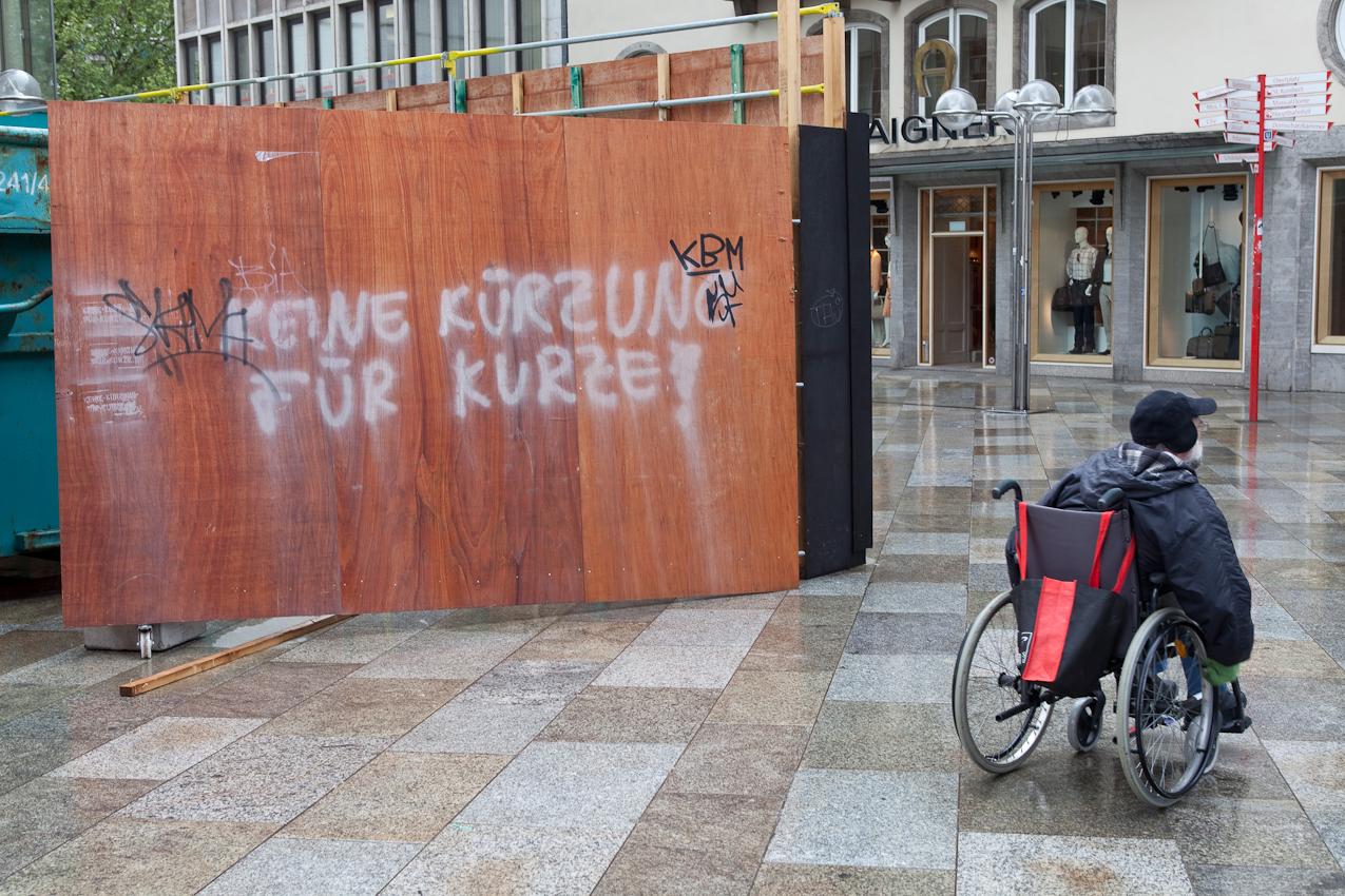 """Ein Rollstuhlfahrer passiert einen Bauzaun auf der Domplatte mit dem Graffiti """"Keine Kürzung für Kurze""""."""