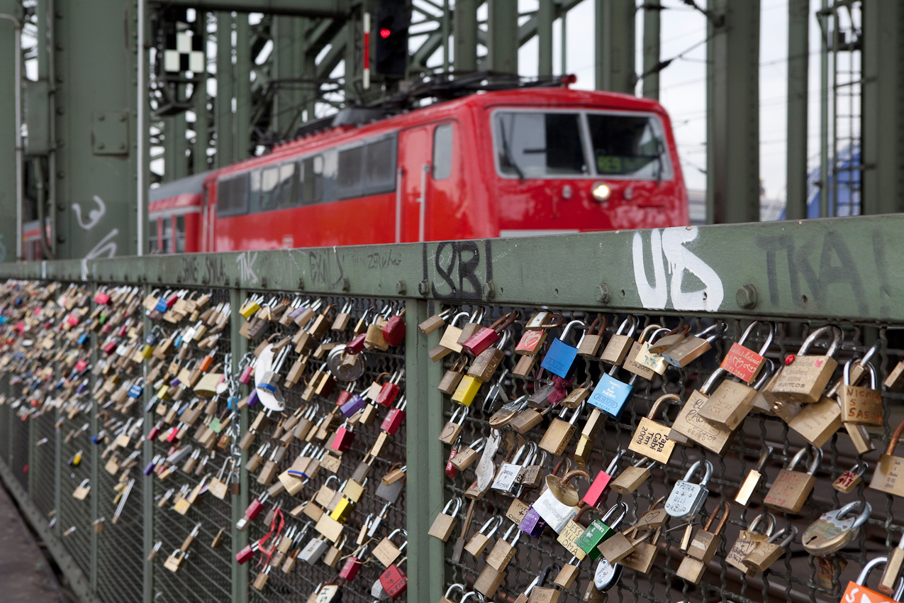 Liebesschlösser in Köln an der Hohenzollernbrücke. Kölner Liebespaare haben den römischen Brauch übernommen, als Zeichen ihrer Liebe und Verbundenheit ein Schloss an die Brücke zu hängen und den Schlüssel in den Rhein zu werfen. Mittlerweile hängen tausende Schlösser an der Brücke und auch Touristen beteiligen sich an dem Brauch.