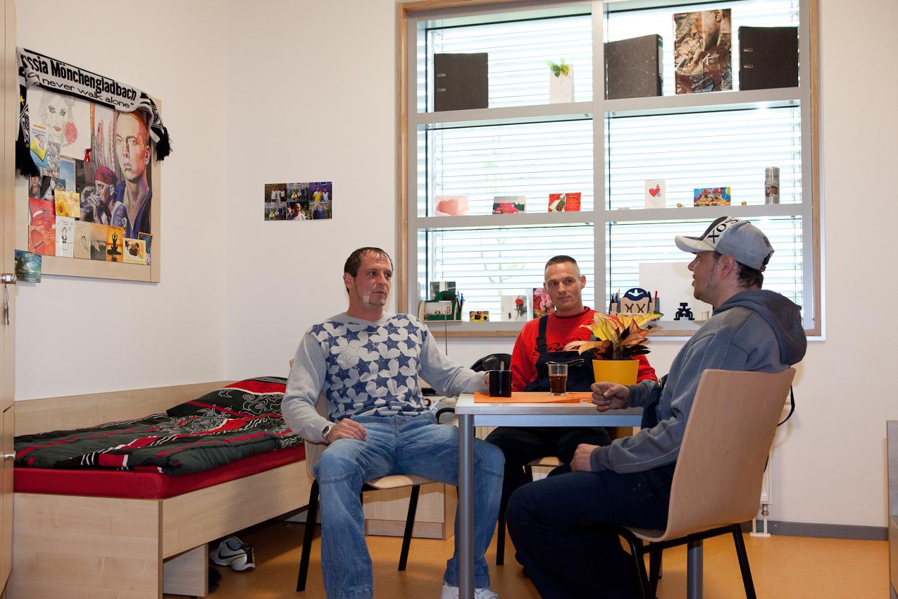 Die Aufnahme zeigt die Patienten Sascha K., Giorgio W. und Marco K. im Zimmer von Sascha. Die drei sind in der Klinik Freunde geworden und sehen den Aufenthalt im Maßregelvollzug als Chance zur Rehabilitation. An der Wand der Fan-Schal von Borussia Mönchengladbach, Grußkarten und Fotos von Saschas Freunden und Bekannten.