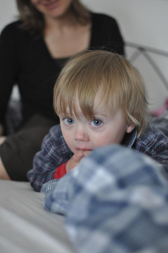 Die 18 Monate alte Magdalena hat ihren Vater erblickt und schaut verwundert, was er macht. Sie hält sich die Finger in den Mund, weil ihre noch nicht ganz vorhandenen Zähnlein schmerzen. Im Hintergrund sitzt ihre Mutter Maria.