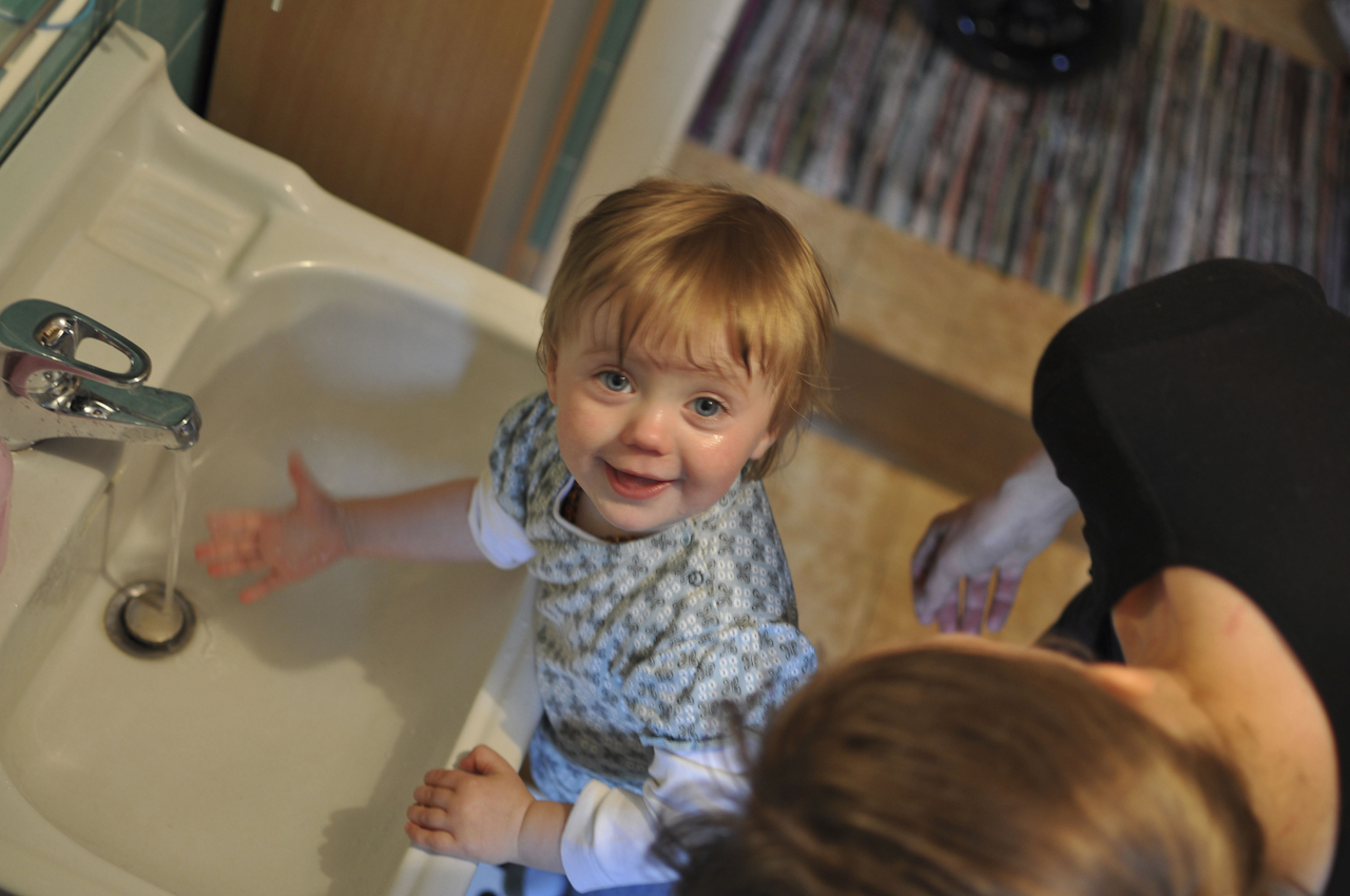 Magdalena wird von Ihrer Mutter Maria beim täglichen waschen unterstützt. Kaum hat die Mutter ihren Blick abgewandt, öffnet Magdalena selber den Wasserhahn und hält ihre Hand darunter. So dicht, dass es spritzt. Morgenwäsche ohne nochmal umziehen ist selten.
