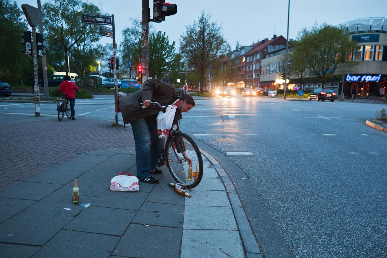 21:03 Uhr, Schanzenviertel: Vorbereitung für das Wochenende. Ein Fahrradfahrer versucht vergeblich, zwölf Bierflaschen mit seinem Fahrrad zu transportieren.