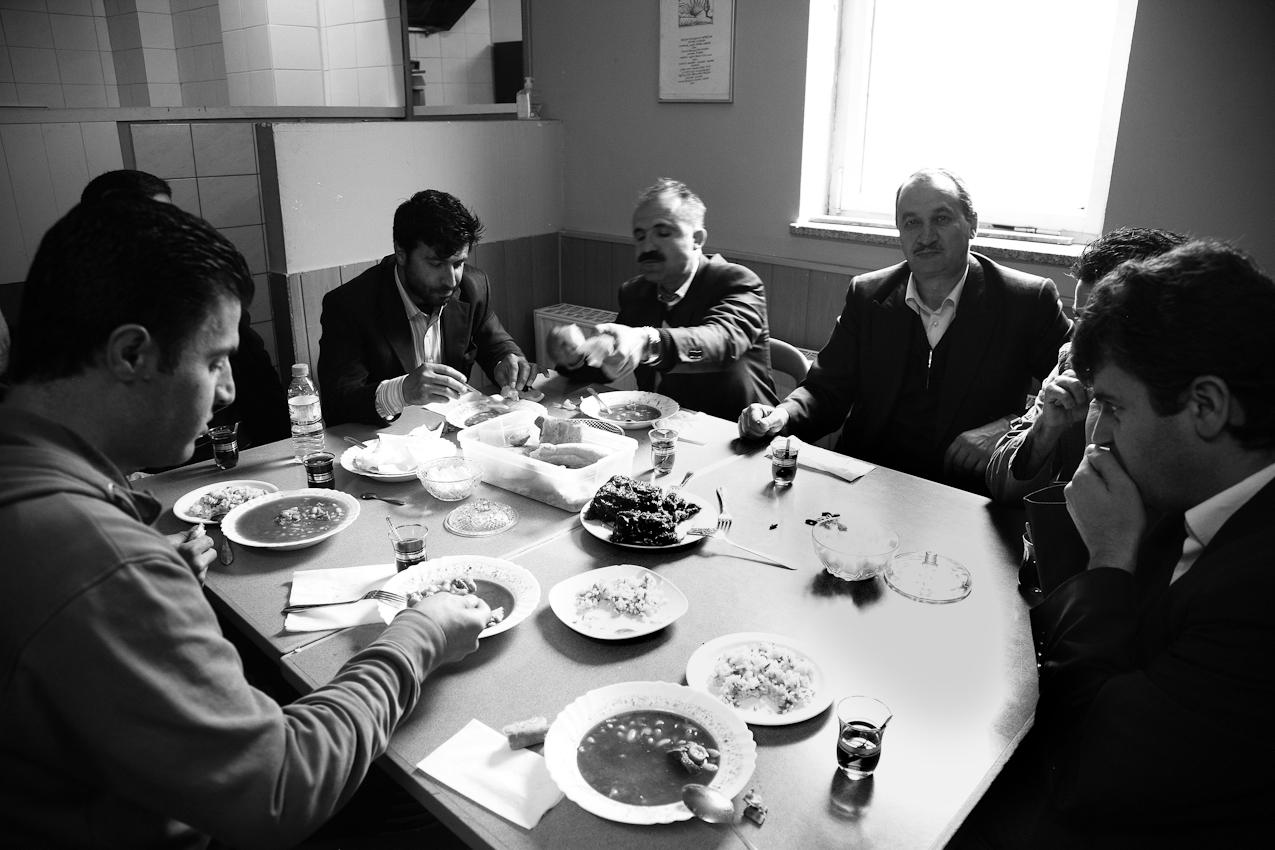 Nach dem Gebet nehmen die Männer noch eine gemeinsame Mahlzeit im Gemeinderaum neben den Gebetsräumen ein. Unter ihnen ist auch der Imam, der in die Kamera schaut. Bei einem Glas Tee werden auch noch die Ereignisse der Woche besprochen, bevor man die Moschee wieder verlässt. Fur viele gestaltet es sich schwierig an diesen sozialen Vorgängen teilzuhaben, da der Freitag in Deutschland ein normaler Arbeitstag ist. In der muslimischen Welt entspricht der Freitag dem christlichen Sonntag und die Geschäfte sind in der Regel geschlossen.
