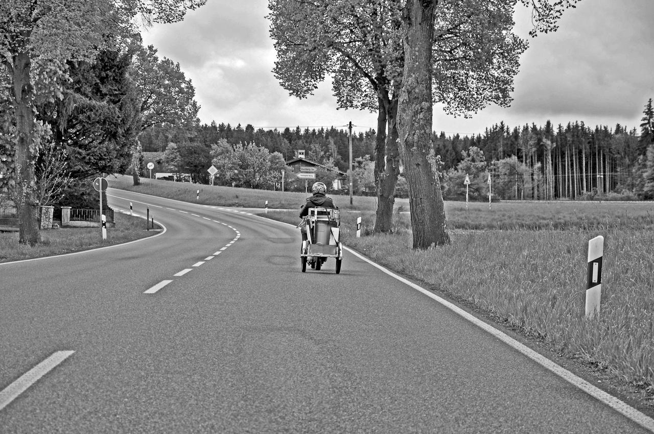 Ein Mofafahrer mit Anhänger fährt mehrmals täglich Schrottteile von Horzing uber die B 304 zur Verwehrtungsstelle bei Matzing.