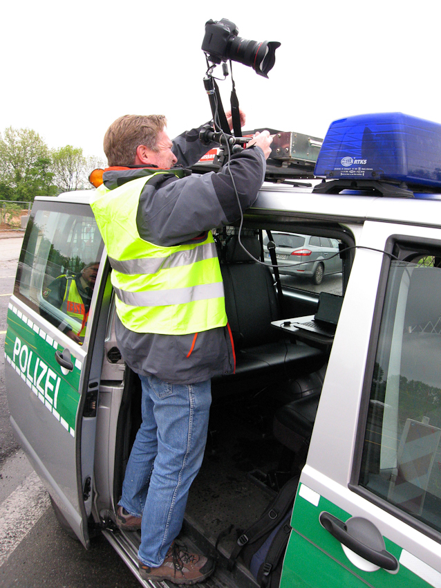 Ein Tag Deutschland. Fotograf Jochen Tack montiert eine Kamera auf das Dach eines Polizeistreifenwagens der Autobahnpolizei, für die Fotos vom Tag auf der A40, Ruhrschnellweg. Die Kamera wird über einen Laptop bedient. Foto: Julia Fischer